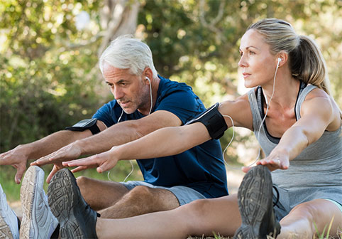 Couple staying fit by stretching before a run outside